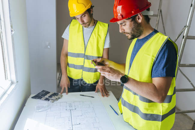 Workers taking a picture of the plan with mobile phone — Stock Photo