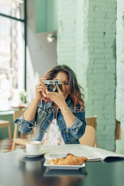 Смеющаяся женщина, сидящая в кофейне и фотографирующая на камеру — стоковое фото