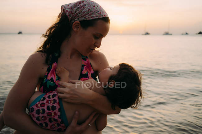 Madre sosteniendo a su hijita en sus brazos frente al mar al atardecer - foto de stock