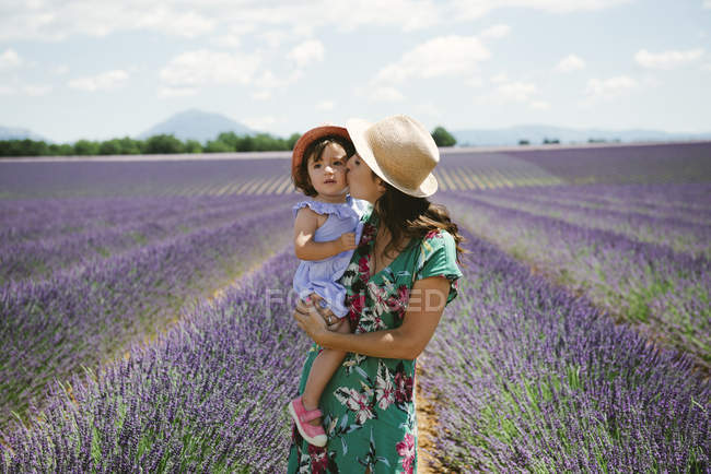 France, Provence, Valensole plateau, Mother kissing daughter in lavender field — Stock Photo
