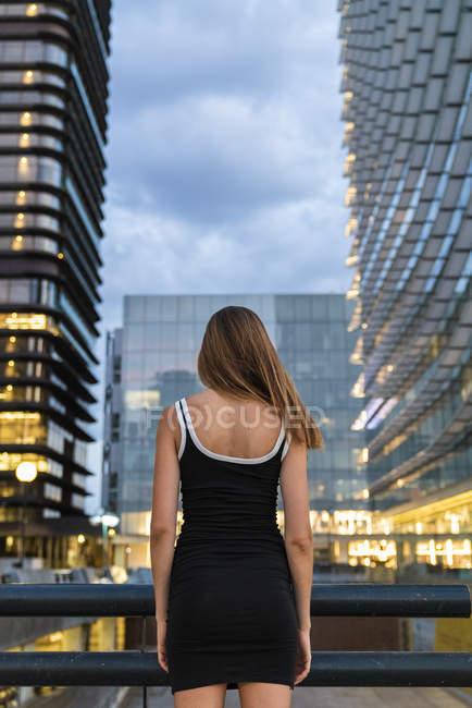 Заднього виду молодої жінки в чорному вбранні в місті в сутінках — стокове фото
