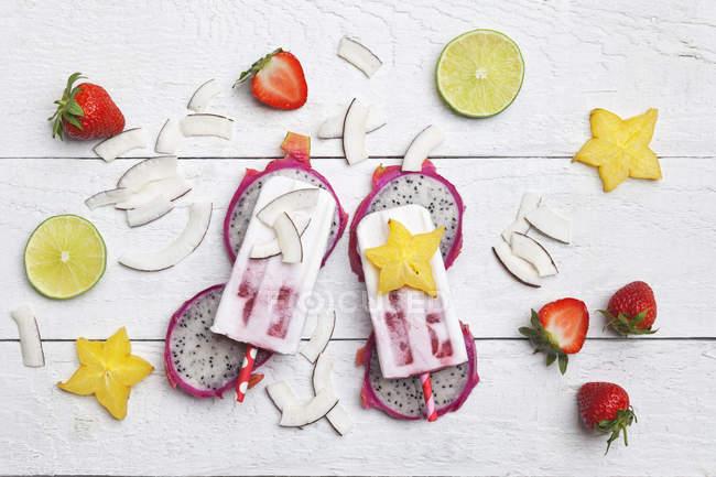 Fruits exocitiques faits maison, sucettes glacées à la noix de coco, fruits étoilés, lime, fruits de dragon, croustilles de noix de coco séchées et fraises — Photo de stock