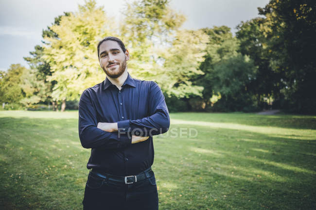 Young businessman standing in park with arms crossed — Stock Photo