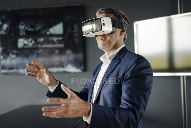 Mature businessman wearing VR glasses in office — Stock Photo