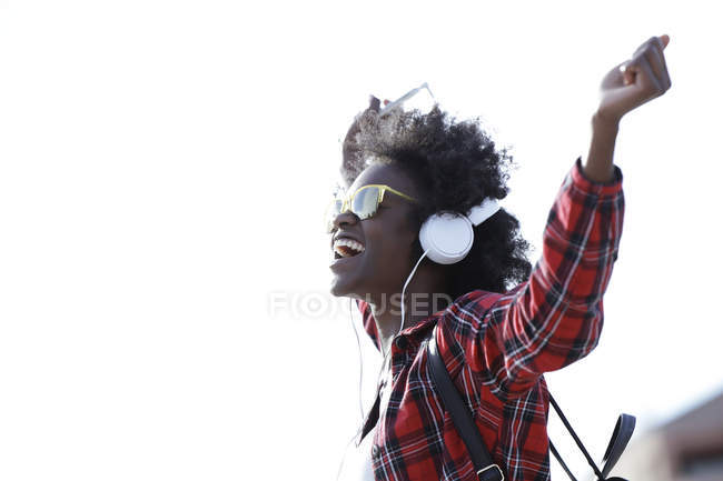 Happy young woman listening music with headphones and cell phone — Stock Photo