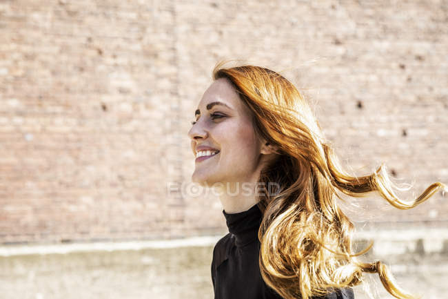Portrait of smiling woman with blowing hair — Stock Photo