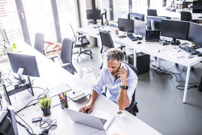 Mature businessman sitting at desk in office and using cell phone and laptop — Stock Photo