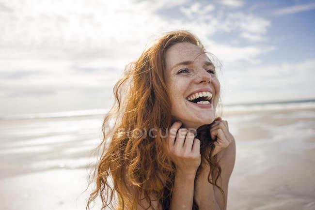 Ritratto di una donna dai capelli rossi, che ride felice sulla spiaggia — Foto stock