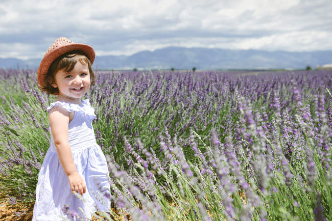 France, Provence, Valensole plateau, Happy toddler girl standing in purple lavender fields in the summer — Stock Photo
