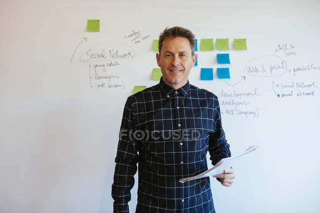 Homme d'affaires confiant debout dans le bureau en face du tableau blanc avec des notes adhésives — Photo de stock