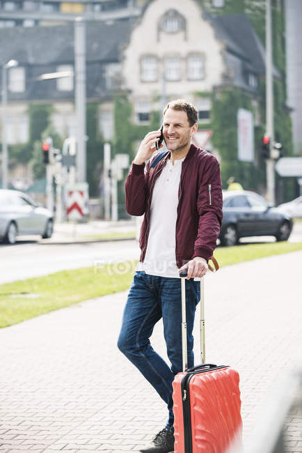 Smiling man with rolling suitcase on cell phone in the city — Stock Photo