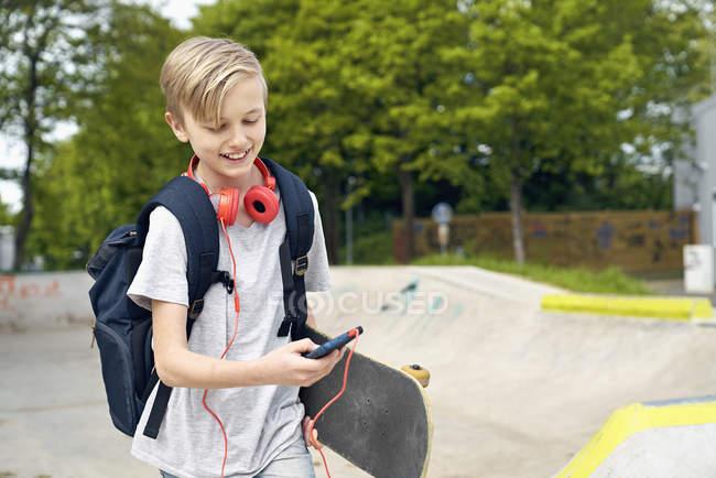 Menino com auscultadores, skate e saco de escola usando o smartphone — Fotografia de Stock