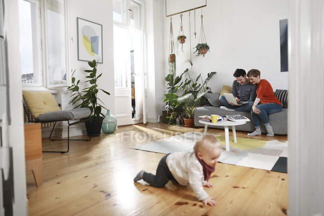 Батьки сидять на дивані, використовуючи ноутбук, поки дочка грає на підлозі — стокове фото