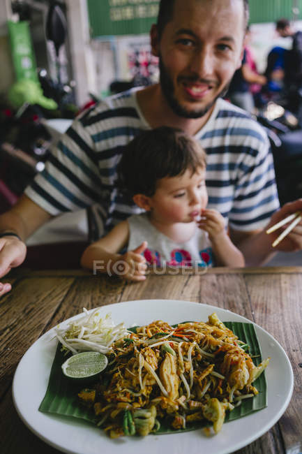 Thailand, Father and daughter eating delicious pad thai dish on a street restaurant — Stock Photo