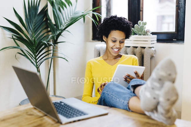 Young african american woman sitting at table with feet up, using digital tablet — Stock Photo
