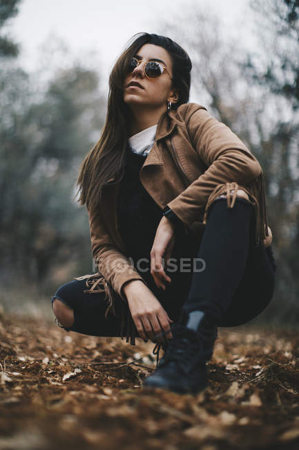 Cool young woman wearing sunglasses and leather jacket crouching on forest soil — Stock Photo