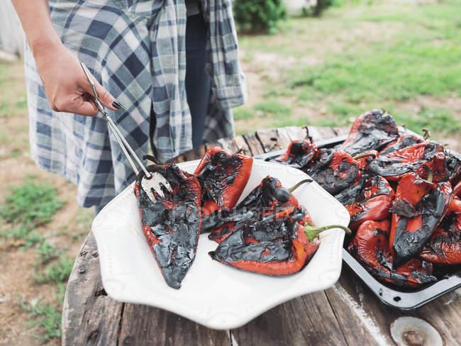 Mano femminile tenuta alla griglia peperone rosso — Foto stock
