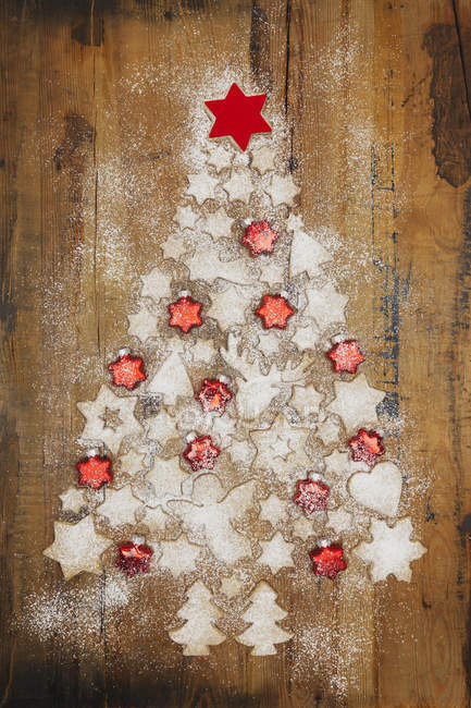 Christmas cookies and red star-shaped Christmas baubles forming Christmas Tree on wooden background — Stock Photo