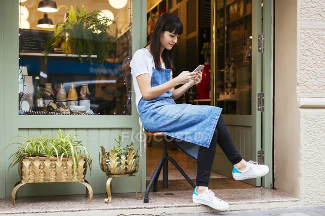 Женщина сидит на стуле, используя мобильный телефон у входной двери магазина — стоковое фото