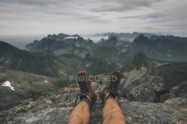 Norway, Lofoten, Moskenesoy, Young man sitting at Hermannsdalstinden, looking over Kjerkefjord — Stock Photo
