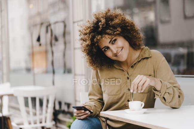 Жінка перед кав'ярнею, п'є каву, тримає смартфон — стокове фото