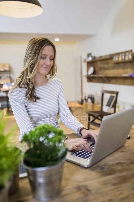Улыбающаяся женщина с помощью ноутбука на деревянном столе дома — стоковое фото