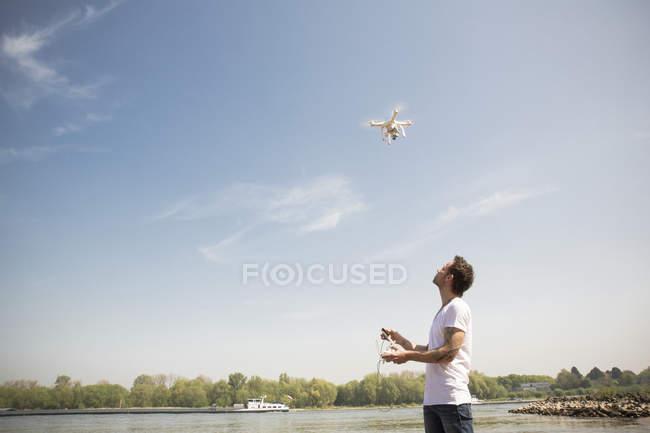 Людина летить безпілотним літаком біля річки. — стокове фото