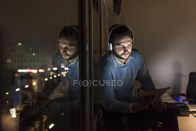 Homme d'affaires assis sur le rebord de la fenêtre dans le bureau la nuit en utilisant tablette et écouteurs — Photo de stock