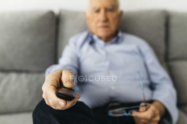 Senior man watching Tv from the couch at home, focused on hand. - foto de stock