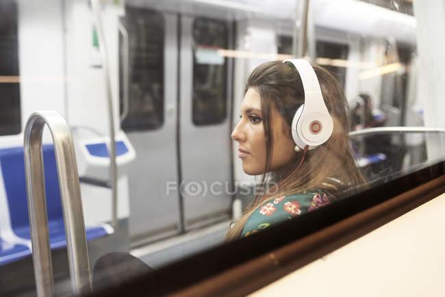 Portrait de jeune femme écoutant de la musique avec des écouteurs dans un train souterrain — Photo de stock