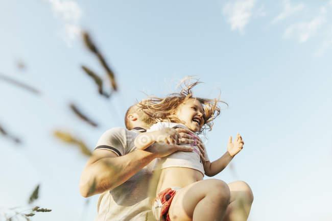 Отец играет со своей маленькой дочерью в природе — стоковое фото