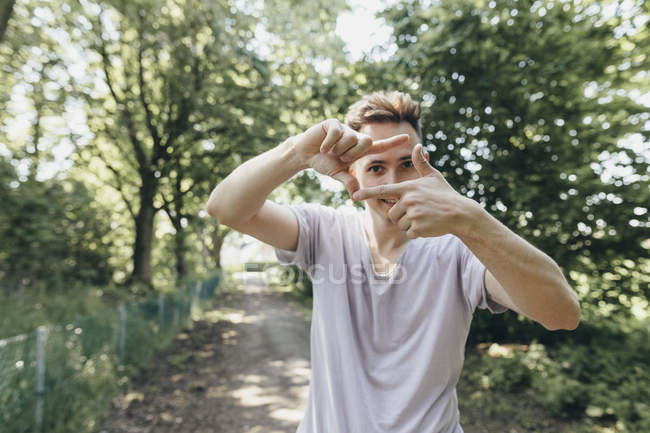 Joven haciendo un marco de dedo en el camino del bosque - foto de stock