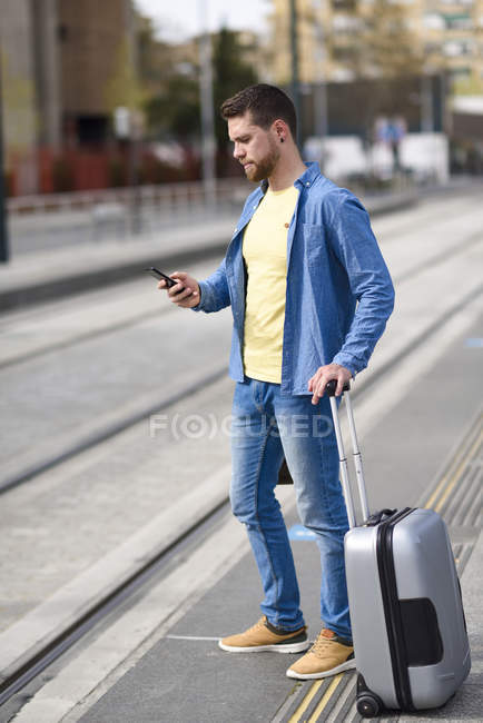 Young man waiting at a station with smartphone in his hand and trolley — Stock Photo