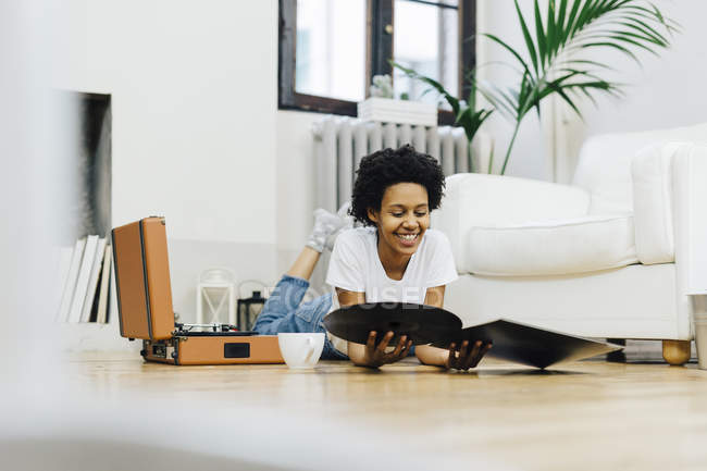 Young african american woman at home listening vinyl records, lying on ground — Stock Photo