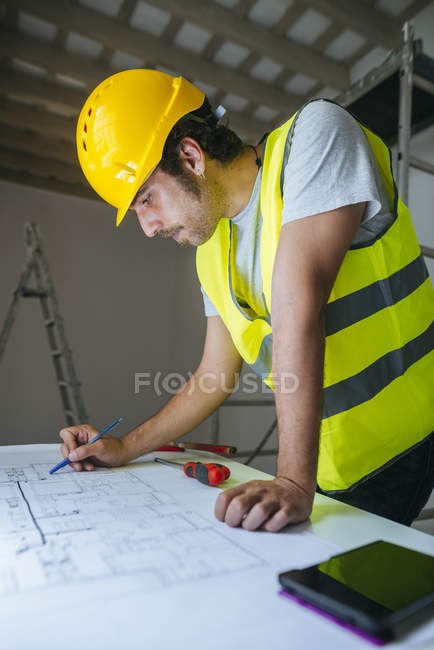 Worker looking at construction plan — Stock Photo