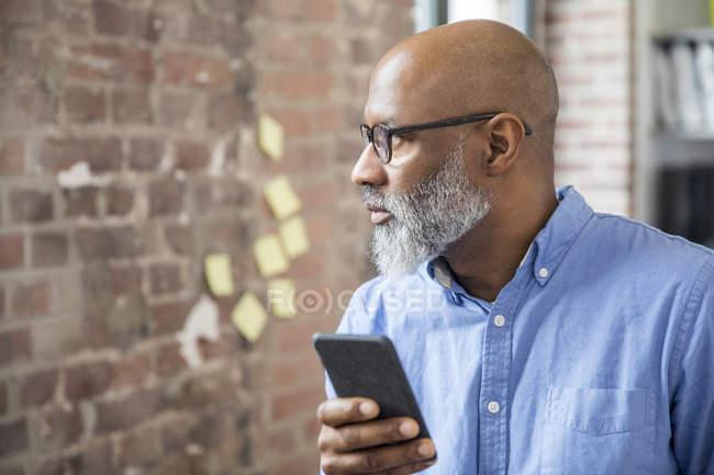 Afro-américain Homme d'affaires avec téléphone portable dans un loft — Photo de stock