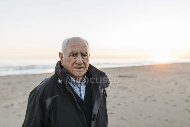 Homem sênior de pé na praia e olhando para a câmera — Fotografia de Stock