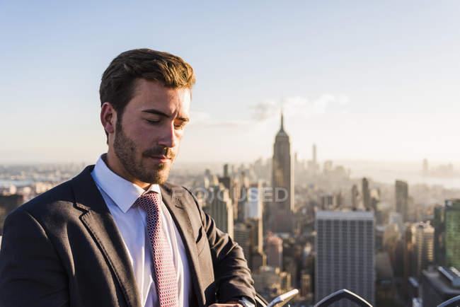 USA, New York, uomo d'affari con cellulare sul ponte di osservazione del Rockefeller Center — Foto stock