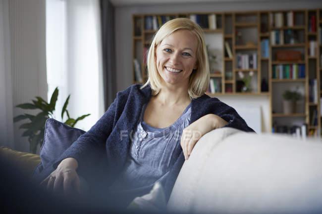 Женщина отдыхает дома, сидит на диване — стоковое фото