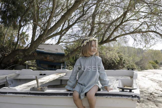 Посміхнена дівчинка з квітами сидить на човні на пляжі. — стокове фото