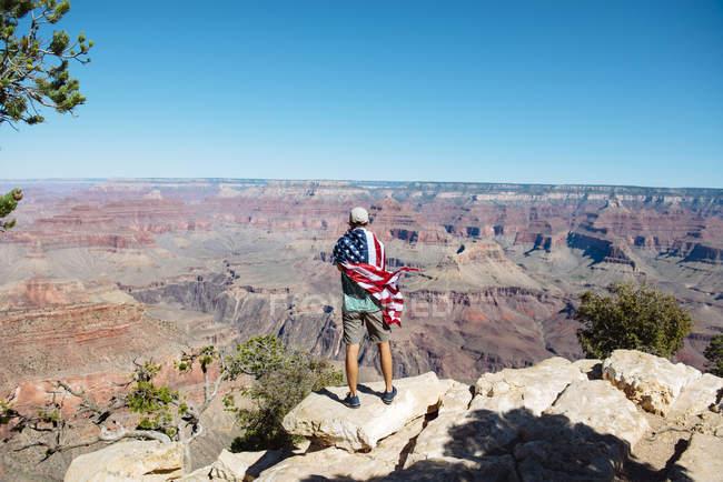 Usa, Arizona, vue arrière d'un homme enveloppé dans un drapeau américain admirant le parc national du Grand Canyon — Photo de stock
