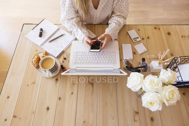Jeune femme assise au bureau, utilisant un ordinateur portable — Photo de stock