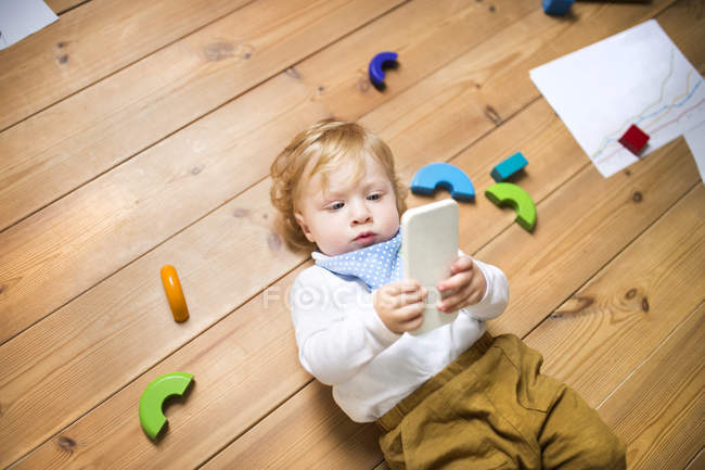 Kleiner Junge spielt zu Hause mit Smartphone — Stockfoto
