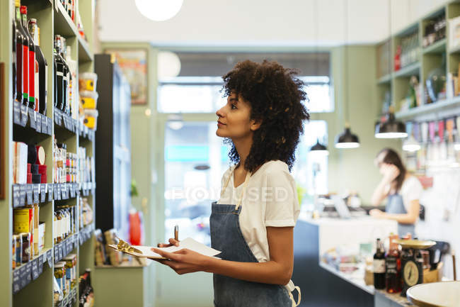 Woman with clipboard at shelf in a store — Stock Photo