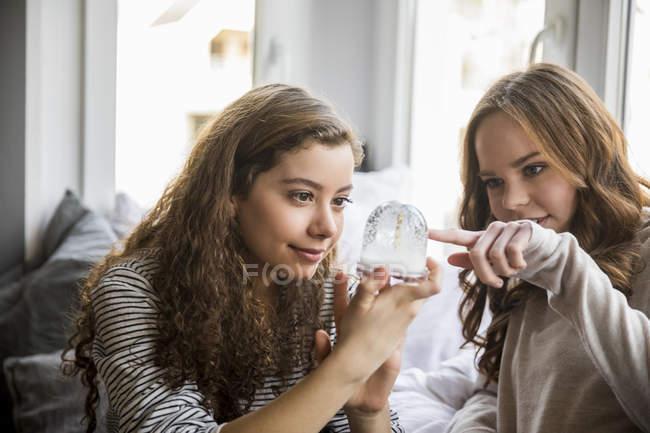 Due ragazze adolescenti con globo di neve a casa — Foto stock