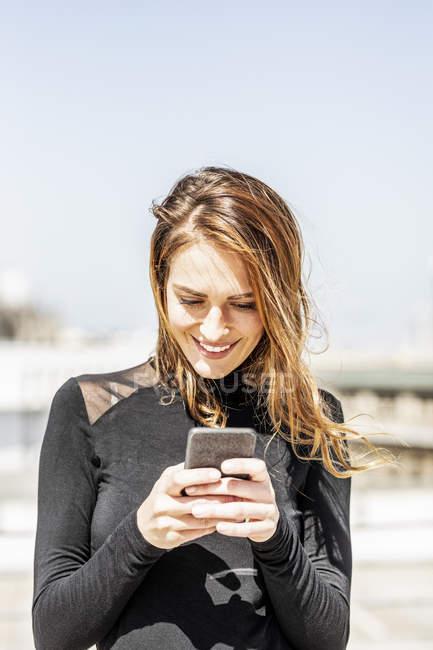 Portrait de femme souriante utilisant un smartphone à l'extérieur — Photo de stock