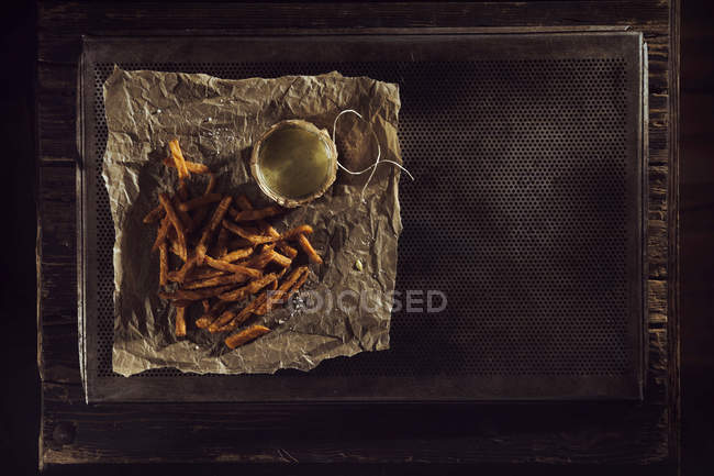 Hand made french fries with mayonnaise on baking paper, baking tray, overhead view — Stock Photo