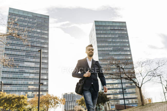 Uomo d'affari che indossa occhiali da sole e cammina fuori dall'edificio degli uffici — Foto stock