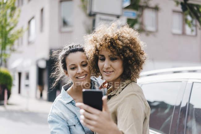 Migliori amici scattare selfie con uno smartphone in città — Foto stock