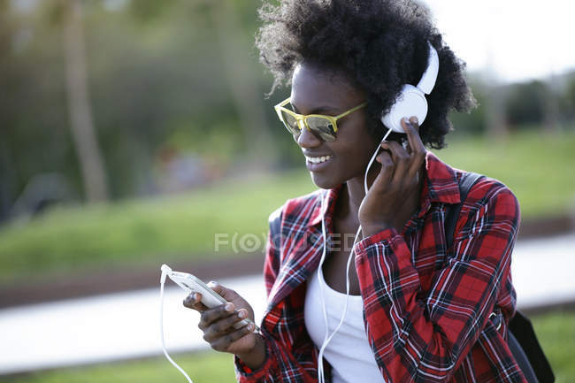 Portrait of happy young woman listening music with headphones and smartphone — Stock Photo